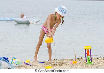 five-year, menina, ligado, um, praia, água derramando, de, um, balde, areia