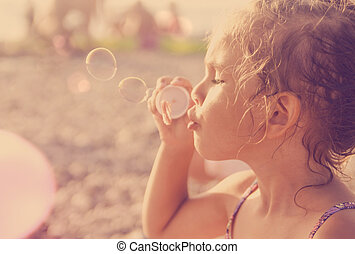 Five year old beautiful little girl blows soap bubbles on a sunny summer beach
