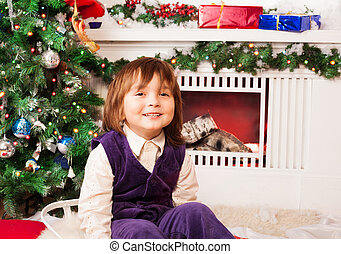 Five year old boy sitting by Christmas tree