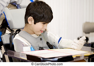 Five year old disabled boy studying in wheelchair