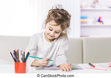 five year old girl draws with crayons sitting at table in the nursery