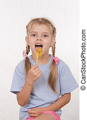 Five year old girl licking a lollipop