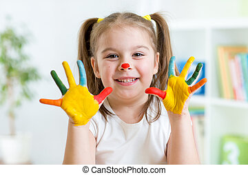 Five year old girl with hands painted in colorful paints...