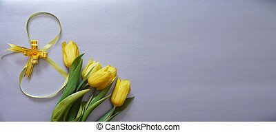 Five yellow tulips on a gray background with the number eight made of ribbon