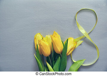 Five yellow tulips on a grey background with the number eight made of ribbon