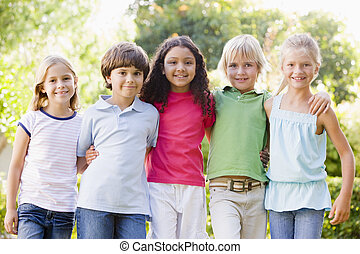 Five young friends standing outdoors smiling