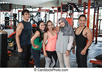 Five young people posing in fitness center showing muscles