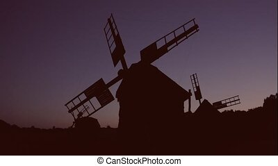 Fixed idle windmills at night. Silhouettes of mills.