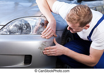 Fixing a car scratch - A man trying to fix a scratch on a...
