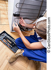 Fixing a refrigerator - A repairman sitting on the floor...
