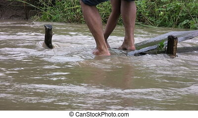 Fixing A Washed Out Foot Bridge - Two men work hard to...