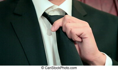Fixing black Tie - man adjusting black tie