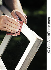 Fixing the Windows. - Man using sandpaper on an old window...