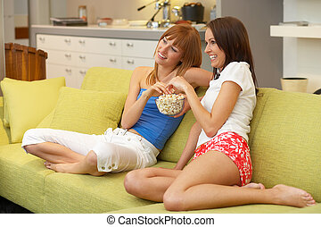 two girls sitting on the couch watching tv