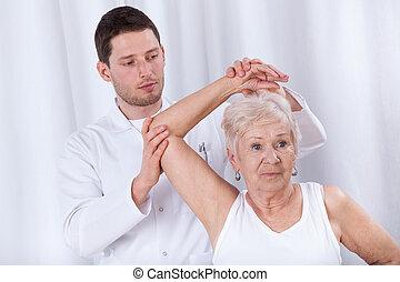 fizykoterapeuta, rehabilitowanie, starsza kobieta