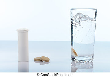 Fizzy vitamin pills and glass of water