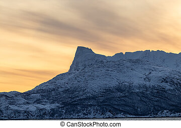 Majestic Norwegian fjord and barren, snow covered mountains during sunset, far above the polar circle near Skjervoy