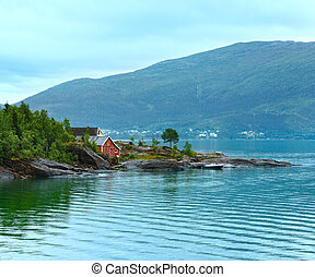 Fjord summer cloudy view with wooden house on coast (Norway)