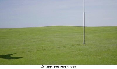 Flag in middle of golf course with slightly worn out green...