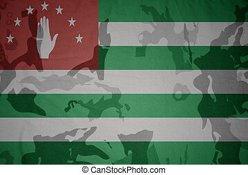 flag of abkhazia on the khaki texture . military concept