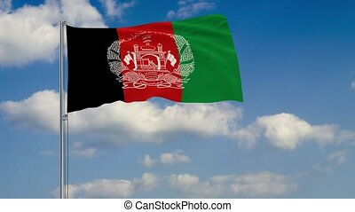 Flag of Afghanistan against background of clouds floating on the blue sky
