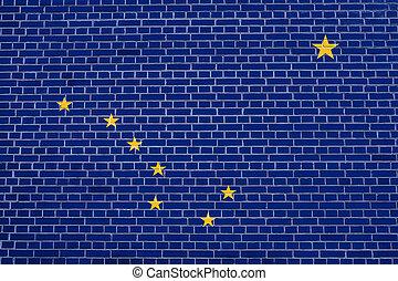 Flag of Alaska on brick wall texture background