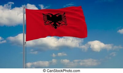 Flag of Albania against background of clouds floating on the blue sky