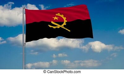 Flag of Angola against background of clouds floating on the blue sky