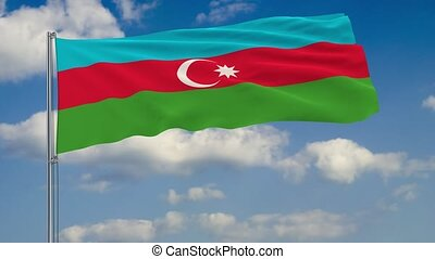 Flag of Azerbaijan against background of clouds floating on the blue sky