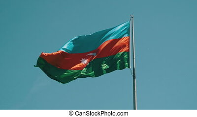 Flag of Azerbaijan on the Flagpole Waving in the Wind Against the Blue Sky