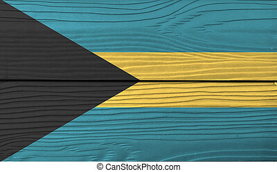 Flag of Bahamas on wooden wall background. Grunge Bahamas flag texture, a horizontal triband of aquamarine (top and bottom) and gold with the black chevron aligned to the hoist-side