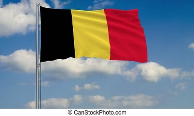 Flag of Belgium against background of clouds