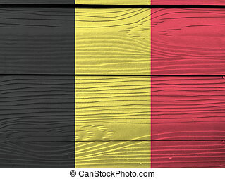 Flag of Belgium on wooden wall background. Grunge Belgium flag texture, a vertical tricolor of black yellow and red.