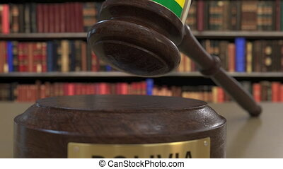 Flag of Bolivia on falling judges gavel in court. National...