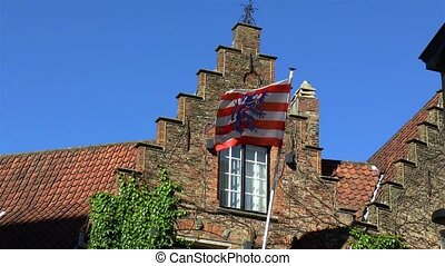 Flag of the City of Bruges, in West Flanders, Belgium, waving at traditional house facade.