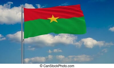 Flag of Burkina Faso against background of clouds floating on the blue sky
