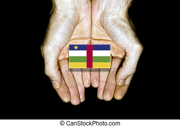 Flag of Central African Republic in hands on black background