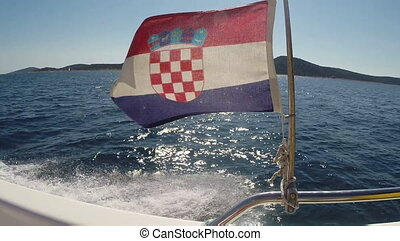Flag of Croatia blowing on a speedboat on the sea