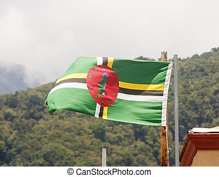 Flag of Dominica flying against a background of tropical hills