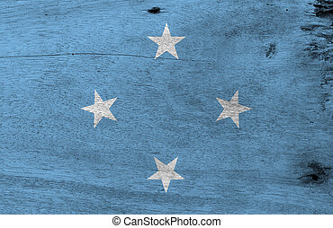 Flag of Federated States of Micronesia on wooden plate background. Grunge Federated States of Micronesia flag texture, A light blue field with four stars arranged in the diamond pattern.