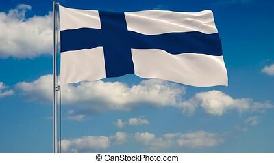 Flag of Finland against background of clouds floating on the blue sky