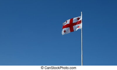 Flag of Georgia country waving in the wind against clear blue sky in sunny day.