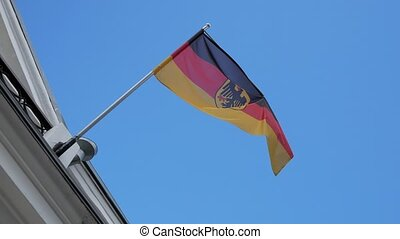 flag of Germany fluttering in the wind against a blue sky