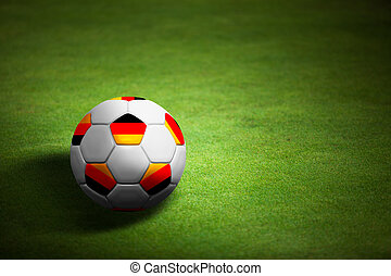 Flag of Germany with soccer ball over grass background -...