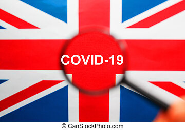 Flag of great Britain with the inscription COVID-19 in a magnifying glass.
