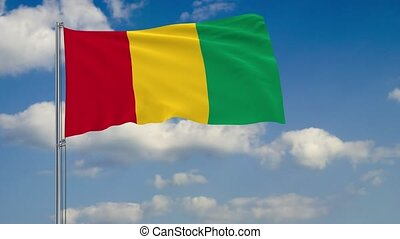 Flag of Guinea against background of clouds sky