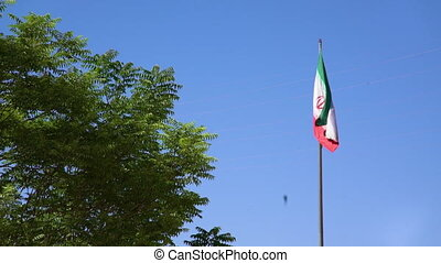 Flag of Iran flaps in the wind against blue sky