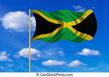 Flag of Jamaica waving on blue sky background