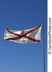 Flag of the Channel Island of Jersey fluttering against a blue sky