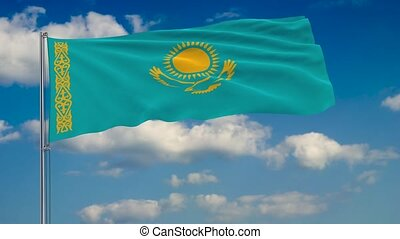 Flag of Kazakhstan against background of clouds floating on the blue sky